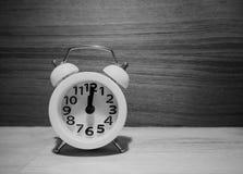 El despertador blanco puso el tablero de la madera, tono blanco y negro foto de archivo libre de regalías