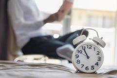 El despertador blanco se fija en una cama y hay una lectura del hombre foto de archivo