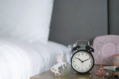 El despertador clásico en el escritorio cerca la cama con otros accesorios femeninos le gusta el unicornio y de las miniaturas de Foto de archivo