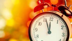 El despertador del vintage está mostrando medianoche Es reloj del ` de doce o, la Navidad y bokeh, concepto festivo de la Feliz A Fotos de archivo