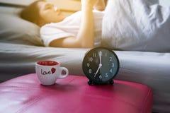 El despertador negro con la mujer asiática de la falta de definición despierta y con el móvil en el dormitorio Imagen de archivo