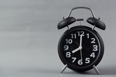 El despertador negro del vintage del color en fondo gris, despierta tiempo Fotos de archivo