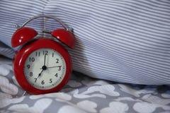 El despertador rojo retro se coloca en la cama fotos de archivo