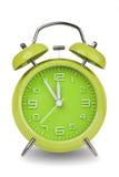 El despertador verde con las manos en 5 minutos labra 12 Imagenes de archivo