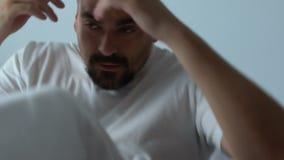 El despertar ansioso del hombre asustado en la noche de la cama, pesadilla, preocupó el sueño, tensión almacen de metraje de vídeo