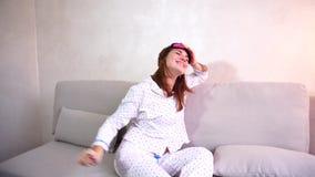 El despertar de la mujer después del sueño en buen humor en dormitorio en buena mañana del sofá almacen de video