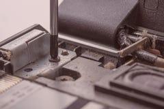 El destornillador desatornilla el perno de sujeci?n del tablero del ordenador del procesador fotografía de archivo