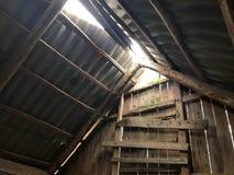 El desván abandonado arruinado viejo con una puerta, el tejado del interior con la pizarra del sol, haciendo su manera a través d Fotos de archivo libres de regalías