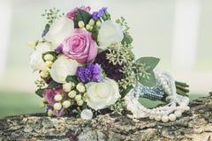 El detalle al aire libre nupcial del collar del ramo y de la perla tiró de la boda Imagen de archivo