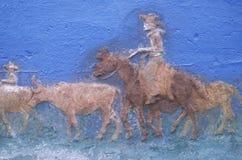 El detalle de la pintura del vaquero en el caballo que redondea encima de ganado en ganado conduce Fotos de archivo libres de regalías