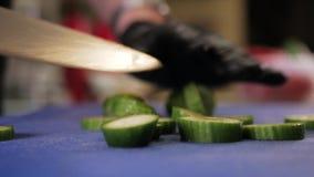 El detalle de las manos que tajan el pepino con el cuchillo in fine junta las piezas a bordo almacen de metraje de vídeo