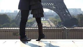 El detalle de pares de los pies de los amantes que fechan la torre Eiffel cercana, el hombre y la mujer aman almacen de metraje de vídeo
