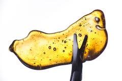 El detalle del fragmento del concentrado del aceite del cáñamo aka sostenido en una herramienta es foto de archivo libre de regalías
