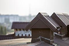 El detalle del primer del nuevo ladrillo construido enyesó las chimeneas en el top de la casa con el tejado de teja del metal Tra imagenes de archivo