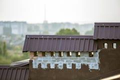El detalle del primer del nuevo ladrillo construido enyesó las chimeneas en el top de la casa con el tejado de teja del metal Tra fotos de archivo libres de regalías