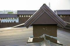 El detalle del primer del nuevo ladrillo construido enyesó las chimeneas en el top de la casa con el tejado de teja del metal Tra fotos de archivo