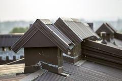 El detalle del primer del nuevo ladrillo construido enyesó las chimeneas en el top de la casa con el tejado de teja del metal Tra fotografía de archivo libre de regalías