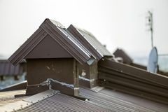 El detalle del primer del nuevo ladrillo construido enyes? las chimeneas en el top de la casa con el tejado de teja del metal Tra imagen de archivo libre de regalías