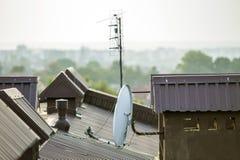 El detalle del primer del nuevo ladrillo construido enyes? las chimeneas en el top de la casa con el tejado de teja del metal Tra fotografía de archivo