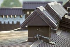 El detalle del primer del nuevo ladrillo construido enyes? las chimeneas en el top de la casa con el tejado de teja del metal Tra imagenes de archivo