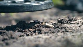 El detector de metales detecta una bala en el cierre de tierra para arriba almacen de video