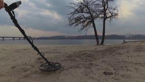 El detector de metales en los bancos del río está buscando las joyas del tesoro en la arena en la playa contra la perspectiva del almacen de video