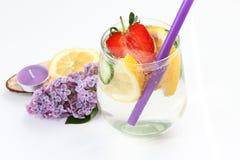 El Detox condimentó el agua con el limón, el pepino y la fresa en el fondo blanco con la lila y la decoración de madera Concepto  imágenes de archivo libres de regalías