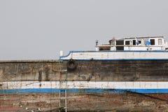 El dhow de madera viejo de Khor Fakkan UAE se lavó para arriba en orilla delante de Khor Fakkport Foto de archivo
