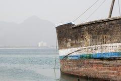 El dhow de madera viejo de Khor Fakkan UAE se lavó para arriba en orilla delante de Khor Fakkport Imagen de archivo libre de regalías