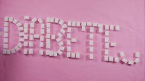 El diabete de la palabra se alinea con los cubos del azúcar refinado en un fondo rosado Concepto de carie almacen de metraje de vídeo
