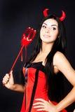 El diablo de la muchacha sostiene la varita mágica Fotografía de archivo libre de regalías