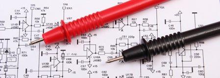 El diagrama de la electrónica imprimió la placa de circuito y el cable del multímetro Fotos de archivo libres de regalías