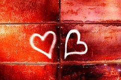 El dibujo de dos corazones en una pared roja para el día del ` s de la tarjeta del día de San Valentín imagen de archivo libre de regalías