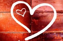 El dibujo de dos corazones en una pared roja para el día del ` s de la tarjeta del día de San Valentín Fotos de archivo