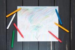 El dibujo de los niños en un fondo de madera oscuro Foto de archivo