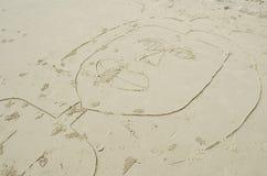 El dibujo de un niño de una mujer en la arena Foto de archivo