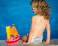 El dibujo del sol de la loción de la protección solar en los niños apoya Foto de archivo libre de regalías