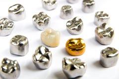 El diente de cerámica, del oro y del metal dental corona en el fondo blanco Foto de archivo