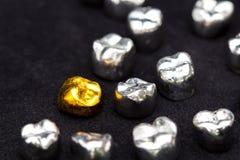 El diente del oro dental y del metal corona en superficie del negro oscuro Imagen de archivo libre de regalías