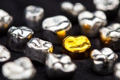 El diente del oro dental y del metal corona en superficie del negro oscuro Foto de archivo libre de regalías