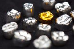 El diente del oro dental y del metal corona en superficie del negro oscuro Fotos de archivo libres de regalías