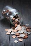 El dinero acuña ahorros del tarro Foto de archivo libre de regalías