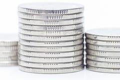 El dinero acuña el aislante de la pila en el fondo blanco Fotos de archivo