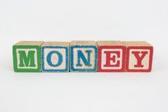 El dinero de la palabra en los bloques de los niños de madera Imagenes de archivo