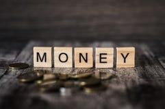 El dinero de la palabra hecho de cubos de madera brillantes con las letras negras de t Fotos de archivo libres de regalías