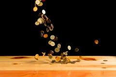 El dinero de las monedas de oro que cae en la tabla de madera con la pared negra, copia s Imagen de archivo