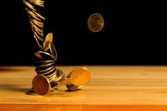 El dinero de las monedas de oro que cae en la tabla de madera con la pared negra, copia s Foto de archivo