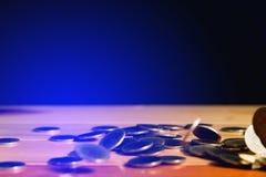 El dinero de las monedas de oro que cae en la tabla de madera con la pared negra, copia s Fotos de archivo