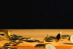 El dinero de las monedas de oro que cae en la tabla de madera con la pared negra, copia s Imagen de archivo libre de regalías