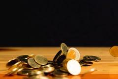El dinero de las monedas de oro que cae en la tabla de madera con la pared negra, copia s Fotografía de archivo libre de regalías